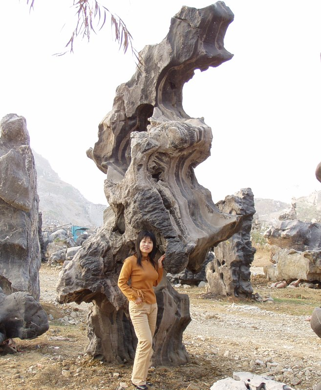 Liuqin standing by natural rock formation in Liuzhou China.